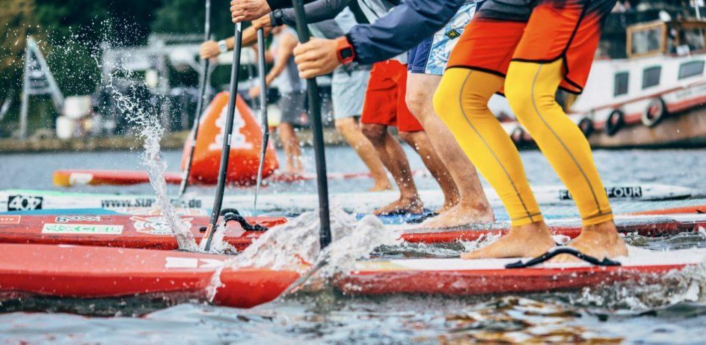 Vier Standup Paddler starten in ein Rennen